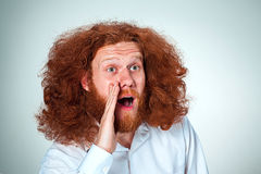 Portrait of screaming young man with long red hair and shocked facial expression on gray background. Portrait of screaming young man with long red hair and with Royalty Free Stock Photos