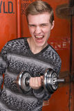 Portrait of screaming young men with dumbbells. Portrait of screaming young man with dumbbells against a red container train Stock Image