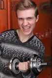 Portrait of screaming young men with dumbbells. Portrait of screaming young man with dumbbells against a red container train Royalty Free Stock Images