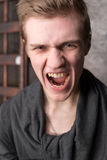 Portrait of screaming young men. Portrait of screaming young man against a dark metal background Royalty Free Stock Images