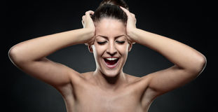 Portrait of screaming young woman with hands on head in black ba Royalty Free Stock Photo