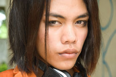 Portrait of SE Asian teenager. Portrait (tightly cropped on the face) of a slightly effeminate long haired emo or punk South East Asian teenage boy with headset Royalty Free Stock Photos