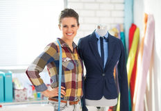 Portrait of seamstress near mannequin in suit Royalty Free Stock Photo