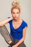 Portrait of a seated blonde woman in jeans Royalty Free Stock Photo