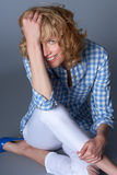 Portrait of seated casual happy young blond fashion model in blu Royalty Free Stock Photo