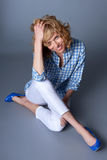 Portrait of seated casual sexy young blond fashion model in blue Stock Photo