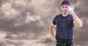 Portrait of security guard holding flashlight against cloudy sky Royalty Free Stock Photo