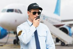 Portrait Of A Security Guard Talking On Walkie Talkie. Portrait Of A Male Security Guard Talking On Walkie Talkie At An Airport stock photos
