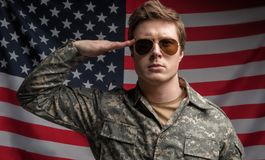 Serious young male officer saluting royalty free stock photography