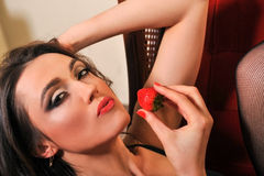 Portrait of seductive beautiful woman posing sexy with strawberry Stock Images