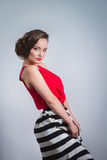 Portrait of seductive beautiful woman in red blouse and striped skirt Stock Photos