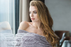 Portrait of seductive blonde female wrapped in grey knitted coverlet Stock Images