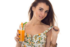 Portrait of seductive brunette girl in summer sarafan with floral pattern drinks orange cocktail and looking at the Royalty Free Stock Photo