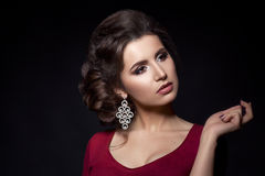 Portrait of seductive brunette woman wearing red dress with neckline and big earrings. Girl with perfect make up and stylish hairc Royalty Free Stock Photo