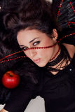 Portrait of a seductive cheeky brunette. With black wings and red apple Royalty Free Stock Images