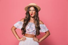 Portrait of seductive european woman 20s wearing straw hat biting lips and holding arms on waist, isolated over pink background i. Portrait of seductive european stock image