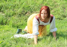 Portrait of a seductive girl. Young seductive woman - brunette sexy girl in white blouse and yellow dress kneeing on meadow with green shoes aside Royalty Free Stock Photo
