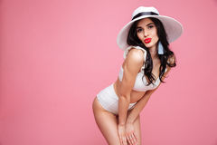 Portrait of a seductive sexy young woman wearing summer hat. Portrait of a sexy young woman wearing beach hat and swimsuit and posing isolated over pink Royalty Free Stock Photo
