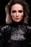 Portrait of seductive woman wearing a sequined black dress. Standing on black background with parted lips royalty free stock photography