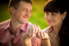 Portrait with selective focus on wedding rings held by smiling c Royalty Free Stock Photography