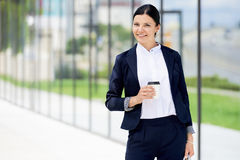 Portrait of self confidence business woman with coffee to go. Next to the office Stock Image