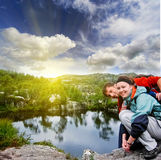Portrait, selfi, happy couple hipster young girl  and man with a beard  in the mountains of Norway, in bright sportswear at sunset Royalty Free Stock Image
