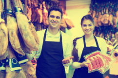 Portrait of sellers offering tasty jamon Royalty Free Stock Photography