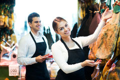 Portrait of sellers offering tasty jamon Royalty Free Stock Image