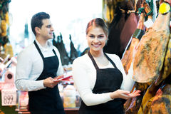 Portrait of sellers offering tasty jamon Stock Images