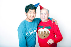 Portrait of a Senior adult man and a young Asian man wearing Christmas jumpers and party hats. Portrait of a Senior adult men and a young Asian men wearing Royalty Free Stock Photo