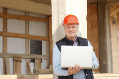 Portrait of senior architect. Senior architect standing in front of building with laptop.  Small business Royalty Free Stock Photo