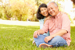Portrait Of Senior Asian Couple Sitting In Park Together Royalty Free Stock Photos