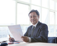 Portrait of senior asian 60s years old working on office table h Royalty Free Stock Image