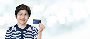 Senior Asian woman with credit card. A portrait of a senior Asian woman with a smile on her face holding up a credit card Royalty Free Stock Images