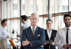 Portrait of senior businessman as leader  with group of people i Stock Photo
