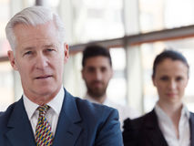 Portrait of senior businessman as leader  with staff in backgrou Stock Photos