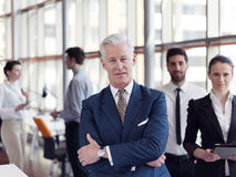 Portrait of senior businessman as leader  with staff in backgrou Royalty Free Stock Photography