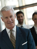 Portrait of senior businessman as leader  with staff in backgrou Royalty Free Stock Images