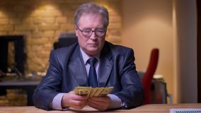 Portrait of senior businessman in formal costume counting money being concentrated and attentive in office. Portrait of senior businessman in formal costume stock video