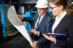 Senior Manager Discussing Factory Plans. Portrait of senior businessman looking at floor plans of modern factory with young assistant manager in workshop stock photo