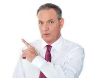 Portrait of senior businessman pointing backwards Royalty Free Stock Image