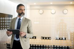 Portrait of senior businessman with tablet in office Stock Photos