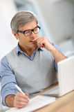Portrait of senior businessman working on laptop Royalty Free Stock Image