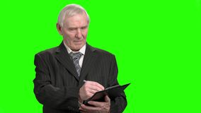 Portrait of senior businessman writing down on clipboard. Old man in suit attentively writing down on clipboard, green hroma background stock video footage
