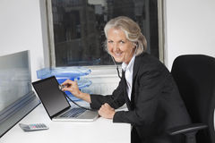 Portrait of senior businesswoman examining laptop with the use of stethoscope at office desk Stock Image