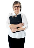 Portrait of senior businesswoman holding reports Stock Photo