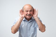 Portrait of senior casual man which overhears conversation over white background. Speak loudly please concept. Royalty Free Stock Photography