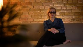 Portrait of senior caucasian lady in 3D glasses sitting on sofa and watching TV attentively in cozy home atmosphere. Portrait of senior caucasian lady in 3D royalty free stock photo