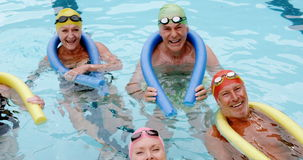 Portrait of senior citizens swimming with inflatable tube stock video