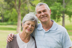 Portrait of a senior couple with arms around at park Stock Images